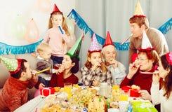 Смеясь над семья поступая в шутку во время партии Стоковое фото RF