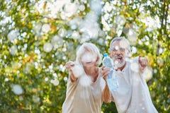 Смеясь над старшии брызгают счастливо воду Стоковое Изображение
