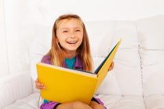 Смеясь над умная девушка с книгой Стоковая Фотография
