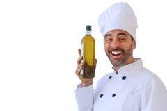 Смеясь над шеф-повар задерживая бутылку оливкового масла Стоковая Фотография