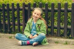 Смеясь над школьница сидя на улице Стоковая Фотография