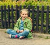 Смеясь над школьница сидя на улице Стоковые Фотографии RF