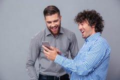 2 смеясь над люд используя smartphone Стоковое Фото