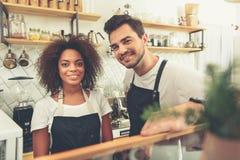 Смеясь над baristas стоя в кухне на стойке Стоковое Изображение