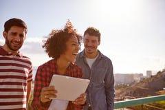 3 смеясь над millennials с таблеткой Стоковая Фотография RF