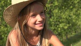 Смеясь ослаблять ребенка на открытом воздухе на траве, счастливом портрете стороны девушки в природе 4K сток-видео