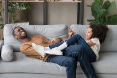 Смеясь смешная игра отца с дочерью лежа на софе стоковое фото rf