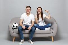 Смеясь футбольные болельщики человека женщины пар веселят вверх по команде поддержки любимой держа bitcoin, будущую валюту, делая стоковое фото