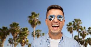 Смеясь человек в солнечных очках над пальмами стоковое изображение rf