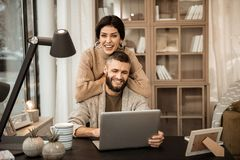 Смеяться апеллирующ женщина полагаясь на задней части ее супруга стоковая фотография