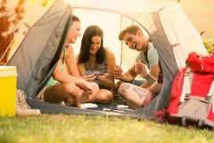 Смеяться и шутка молодых людей пока сидящ в шатре стоковое изображение