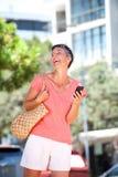 Смеяться над более старой женщины идя снаружи с мобильным телефоном Стоковые Фотографии RF