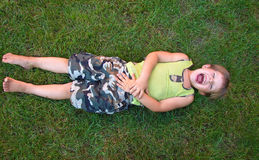 Смеяться над младенца, лежа на траве стоковые фотографии rf