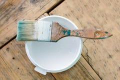 Смогите белой краски и щетки подготовленных для красить деревянную поверхность стоковая фотография