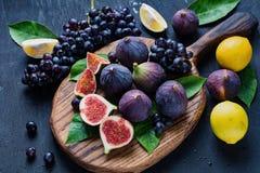 Смоквы, черные виноградины и лимоны Плита свежих фруктов стоковая фотография rf