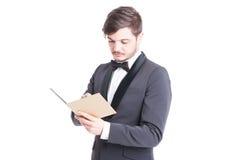 Смокинг и bowtie красивого человека нося смотря тетрадь Стоковая Фотография RF
