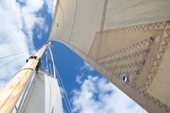 Смотреть вверх рангоут на плавая яхте; сфокусированный на отверстии в ветриле стоковое изображение rf