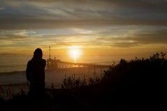 смотреть вне заход солнца силуэта пристани персоны к Стоковое Изображение