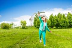 Смотреть девушку держит игрушку самолета с одной ногой вверх стоковая фотография