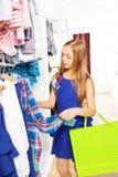 Смотреть девушку с яркой хозяйственной сумкой в магазине Стоковое Фото