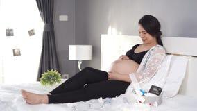 Смотреть и Пэт беременной женщины ее живот на кровати видеоматериал