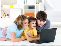 смотреть компьтер-книжки семьи ребенка Стоковое фото RF