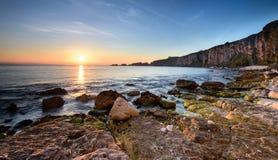 Смотреть к Carrick-a-Rede от пляжа известняка на зоре Стоковое Изображение RF