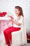 Смотреть молодой красивой девушки счастливый на ее присутствующей коробке Стоковое Изображение RF