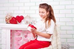 Смотреть молодой красивой девушки счастливый на ее присутствующей коробке Стоковое Фото