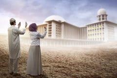 Смотреть молодых мусульманских пар моля к мечети Стоковые Изображения