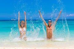 Смотреть пар пляжа Счастливые молодые пары лежа на песке под солнцем Стоковое Фото