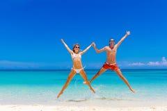 Смотреть пар пляжа Счастливые молодые пары лежа на песке под солнцем Стоковая Фотография