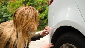 Смотреть поврежденный корабль Блондинка женщины проверяет повреждение автомобиля после аварии 4k, замедление видеоматериал