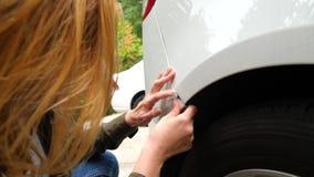 Смотреть поврежденный корабль Блондинка женщины проверяет повреждение автомобиля после аварии 4k, замедление акции видеоматериалы