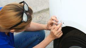 Смотреть поврежденный корабль Блондинка женщины проверяет повреждение автомобиля после аварии сток-видео