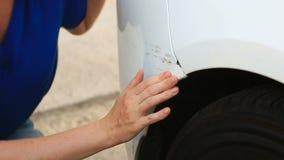 Смотреть поврежденный корабль Блондинка женщины проверяет повреждение автомобиля после аварии акции видеоматериалы