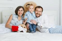 смотреть семьи дочи камеры кровати предпосылки серый счастливый лежащ parents Стоковые Фото