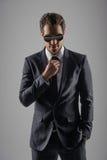 Смотреть совершенный в его новом костюме. Уверенно молодые бизнесмены внутри стоковая фотография