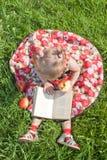 смотреть травы девушки еды книги яблока Стоковые Изображения RF