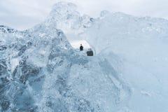 Смотреть через айсберг на туристах в Исландии стоковые изображения