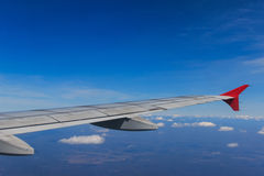 Смотреть через воздушные судн окна во время полета в крыло с славным голубым небом Стоковое Фото
