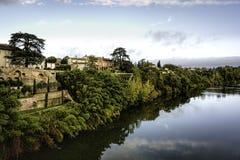 Смотреть через реку Тарна в Lisle-sur-Тарне под wirh голубых небес разбросал облака Стоковая Фотография RF