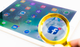 Смотреть через лупу на применении Facebook на iPad стоковое изображение