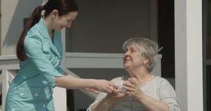 Смотритель дома престарелых дает чашку кофе счастливому пенсионеру усмехаясь совместно на съемке солнечного дня на красной камере акции видеоматериалы