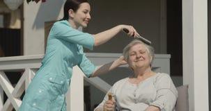 Смотритель расчесывает волосы к старшей женщине на доме престарелых заботясь для пожилых людей на съемке солнечного дня на красно акции видеоматериалы