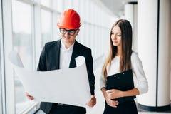 Смотрят, что бумажного архитектора бизнес-леди плана в офисе обсуждают архитекторы бизнесмена проекты дела Arhitect объясняет dea Стоковое фото RF