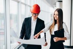 Смотрят, что бумажного архитектора бизнес-леди плана в офисе обсуждают архитекторы бизнесмена проекты дела Arhitect объясняет dea Стоковое Фото