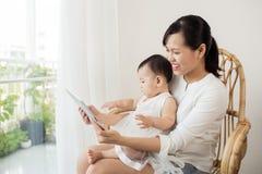 Смотрят, что играют и читают мать и младенец планшет на стоковые изображения rf
