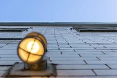 Смотрящ вверх высокорослую внешнюю стену, с запачканным светильником выхода на переднем плане стоковое фото rf