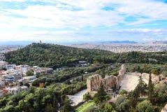 Смотрящ вниз на иконическом старом театре Аттика Herodus около холма акрополя, центра Афин исторического с крышами Афин стоковые фотографии rf